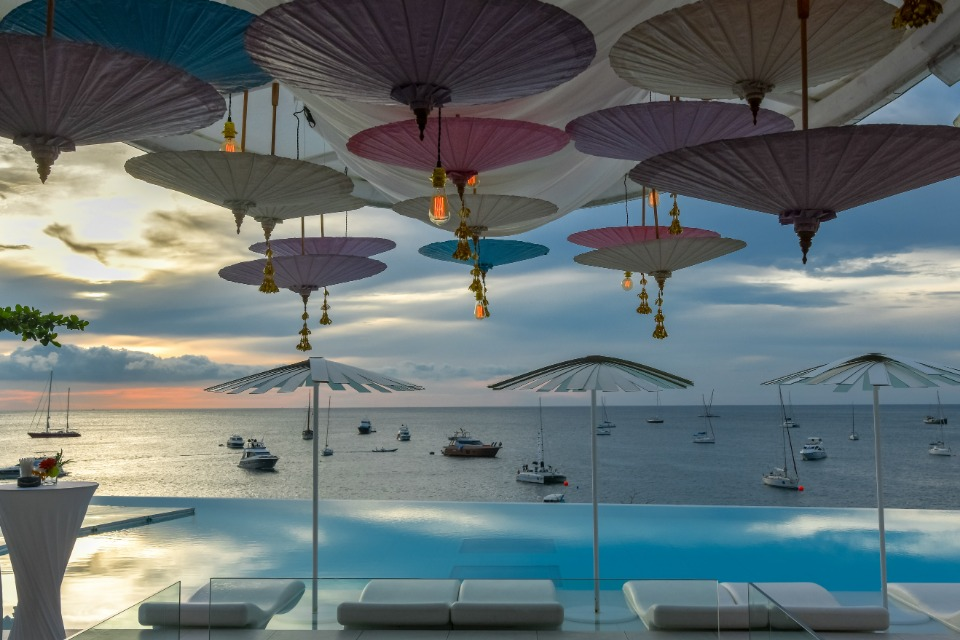 Impressive line-up of superyachts with Thai umbrellas and a spectacular Phuket sunset in the background